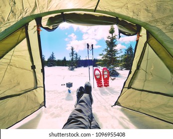Resting in tent while winter hiking. View from the inside of the tent to  winter mountains. The traveler relaxes. The legs of the tent