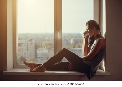 Resting and thinking woman. Calm girl with cup of tea or coffee sitting and drinking on the window-sill at home. Side view. Young attractive multi-racial Asian Caucasian lady in casual clothes resting