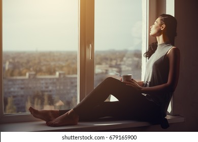 Resting and thinking woman with closed eyes. Calm girl with cup of tea or coffee sitting on the window-sill at home. Side view. Young attractive multi-racial Asian Caucasian lady in casual clothes