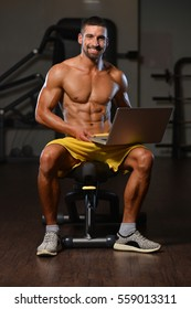 Resting Time - Confident Muscled Young Man Resting In Healthy Club Gym And Using Laptop