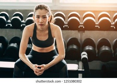 Resting time. Handsome young women in sports sitting at gym