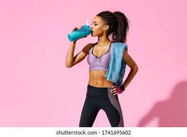Resting time. Sporty girl with towel on shoulders drinks protein cocktail. Photo of african american girl with perfect body on pink background. Strength and motivation