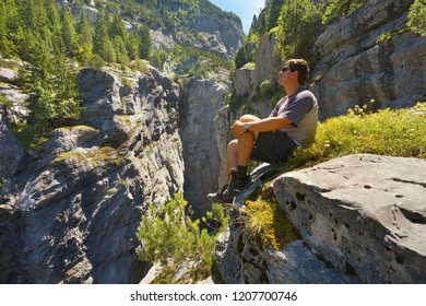Resting tourist watching a deep limestone gorge Gletscherschlucht nearby resort of Grindelwald, Switzerland