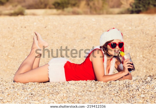 Resting woman on winter vacation in warm places. Beautiful brunette young woman smiling portrait in red Christmas hat celebrating New Year.