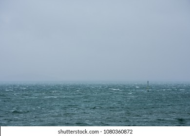 Restless sea and signal light on a vertical stick, with horizon lost in a fog, on a cold, cloudy day