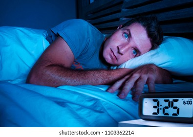 restless worried young attractive man awake at night lying on bed sleepless with eyes wide opened suffering insomnia sleeping disorder depressed and sad in rest privation stress concept