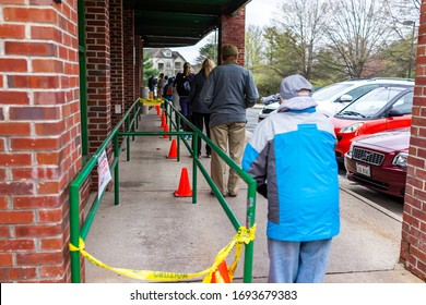 Reston, USA - April 1, 2020: Social distancing of people waiting standing in line by Trader Joe's grocery shop store due to limit for customers at covid-19 coronavirus outbreak epidemic