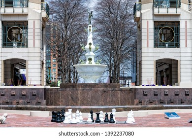Reston, USA - April 11, 2018: Town center building architecture sidewalk street road during day in northern Virginia with water fountain