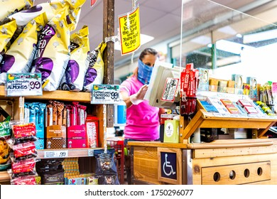 Reston, USA - April 9, 2020: Social distancing sign at cashier check-out aisle inside Trader Joe's grocery shop store during coronavirus with woman employee in mask