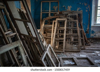restoration of the historic building with the replacement of old wooden window frames with new ones, many removed frames lying on the shabby dirty floor waiting for disposal and recycling