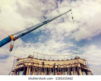 Restoration work of a historical monument of architecture. Crane and scaffolding against a blue sky with clouds.