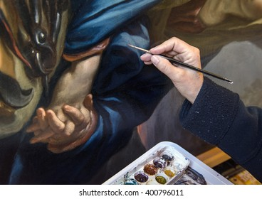 Restoration works on a painting: professional retouches the pigmented surface to remove all the imperfections