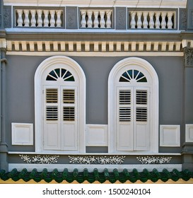 Restored grey traditional pernanakan building with two ornate white arched windows.