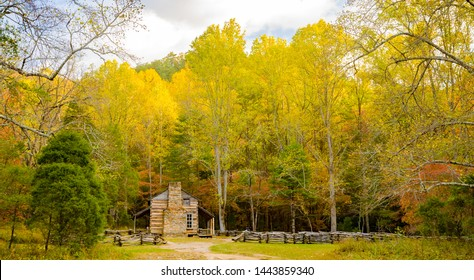 a restored log cabin surrounded by trees showing fall colors and a split rail fence, in the Cades Cove region of the Great Smoky Mountains National Park, Tennessee