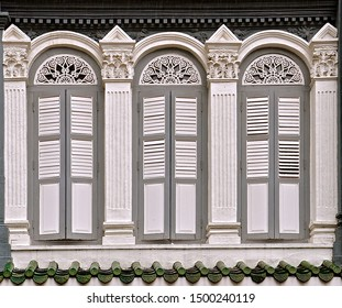 Restored peranakan shop house with three ornate grey french windows with closed wooden louvred shutters.