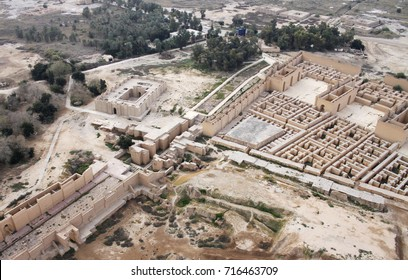 Restored ruins of the South palace of Nebuchadnezzar in ancient Babylon, Iraq on the right. Ruins of the North palace damaged by US occupation on the left. Beyond Processional Street is Ninmah temple.