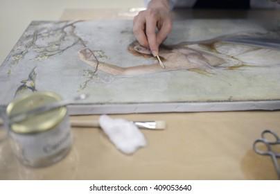 Restorer working old painting restoration.
