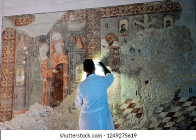 Restoring artisan, with his back to lens, repairing some medieval wall frescoes that were covered with cement decades ago, Church of São Sebastião, Terceira island, Azores. November, 2018