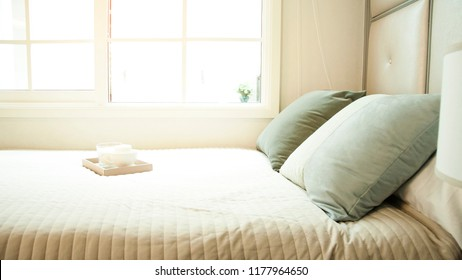 Rest,relax, interior, comfort and bedding concept - bed at home bedroom. Comfortable white bed. Bed maid-up with pillows and bed sheets in beauty room.