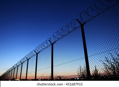 Restricted area fence against dark blue sky
