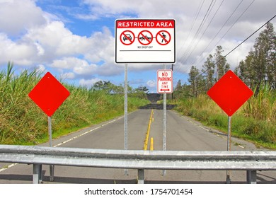 Restricted area - no drop off - no parking any time road sign with 2 red stop signs in front of black lava blocking the road. Big Island, Hawaii.