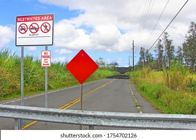 Restricted area - no drop off - no parking any time road sign with red stop sign in front of black lava blocking the road. Big Island, Hawaii.