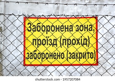 restricted area, passage prohibited (closed), no entrance or crossing sign board on vintage metal grid with barbed wire on ukrainian language
