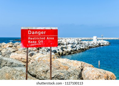 A restricted area sign posted on a breakwater intended to prevent pedestrian injury and to ensure safety.