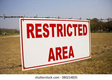 Restricted area sign, red words on white background and  barbed wire