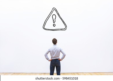 restrictions or alert concept in business, businessman looking at danger sign on white background