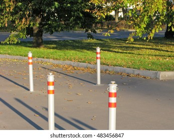 Restrictive fence out of fluorescent poles on sidewalk.
