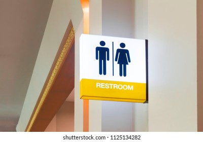 Restroom sign or toilet sign made of electric light box with man and woman icon set  symbol on white concrete wall background, modern, hygiene and clean restroom concept