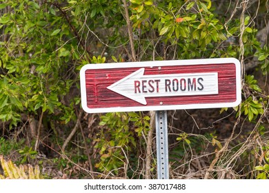Restrooms sign against green background.