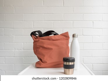 Resuable coffee cup, insulated drink bottle and shopping tote bag on white table against brick wall with copy space
