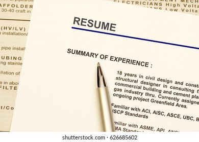 Resume  or curriculum vitae with newspaper ads as background.