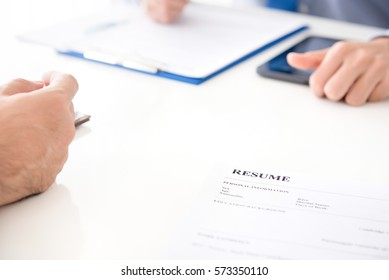 Resume document on the table beside businessmen - job application concept