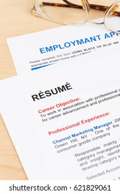 Resume and employment application form with glasses; documents are mock-up