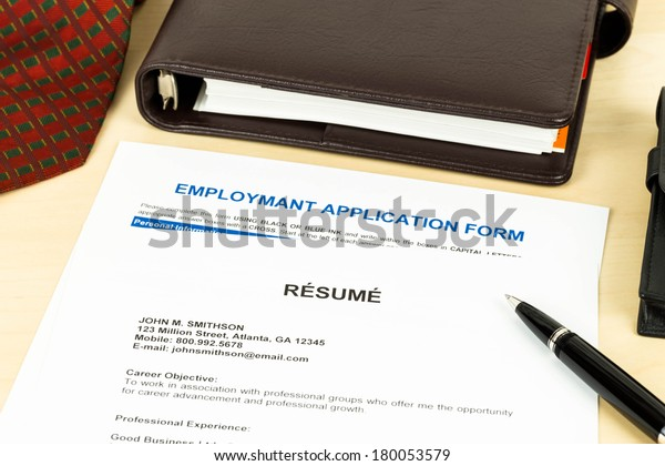 Resume with employment application form, pen, neck tie, and notebook