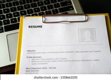 Resume on a clipboard with office table background. A hiring or employment concept