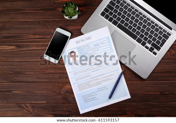 resume phone laptop on wooden table stock photo  edit now  611593157