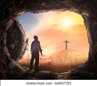 Resurrection of Jesus Christ concept: Human standing with empty tomb stone and cross at sunrise background