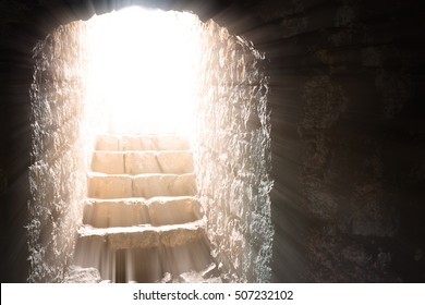 Resurrection of Jesus Christ. Religious Easter background, with strong light rays shining through the entrance into the empty stone tomb. Artistic strong vignette, contrast, dramatic dark-light edit.