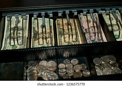 A retail cash drawer in open displaying various types of US currency money and change from cashiers point of view. Grain visible at 100%