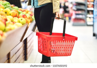 Retail, sale and consumerism concept. Customer in supermarket vegetable and fruit section choosing healthy food. Woman holding shopping basket in grocery store aisle. Student buying groceries.