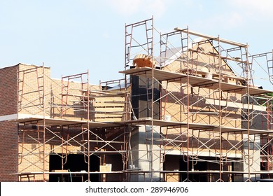 Retail shopping center under construction.  Image shows brick work and scaffolding.