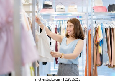 retail shopping concept, Beautiful Asian Thai girl chooses clothes in a shopping mall, Brown hair Smiling women Trying on a blouse, she is very happy after work in the business park near her office