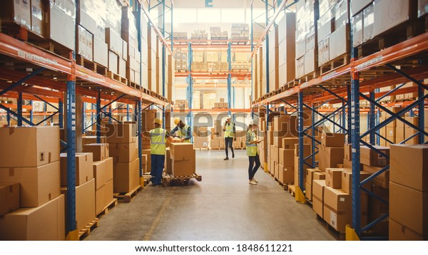 Retail Warehouse full of Shelves with Goods in Cardboard Boxes, Workers Scan and Sort Packages, Move Inventory with Pallet Trucks and Forklifts. Product Distribution Delivery Center.