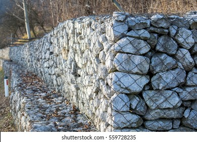 Retaining stone wall next to the road.Steel mesh of gabion wall.