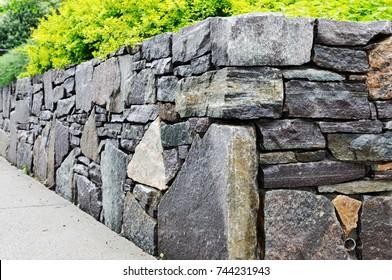 Details der Wand bleiben erhalten. Nahaufnahme einer mit Naturflagsteinen und Wandsteinen von unregelmäßigen Formen und Größen erbauten, aus Naturstein errichteten Mauer aus Trockenstein