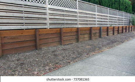 Retaining wall with fence above and bark dust and sidewalk in suburb